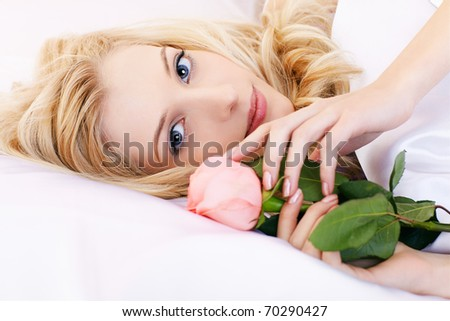 portrait of beautiful happy blonde girl relaxing in bedroom on linen with pink rose - stock photo