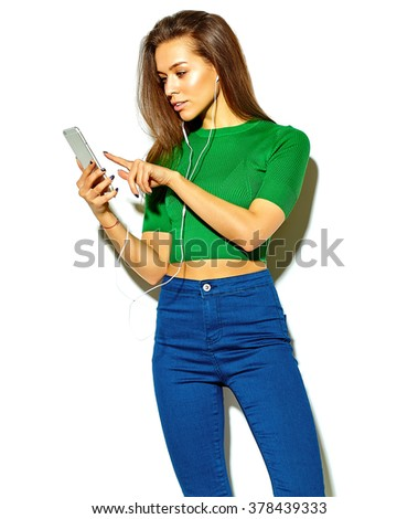 portrait of beautiful happy cute brunette woman girl in casual green hipster summer clothes with no makeup isolated on white using a smart phone
