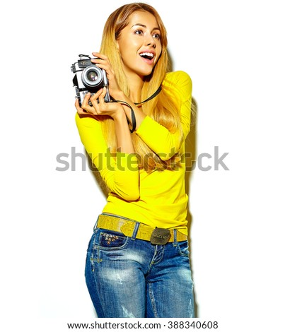 portrait of beautiful happy cute smiling blond woman girl in casual summer clothes takes photos holding retro photographic camera, isolated on a white