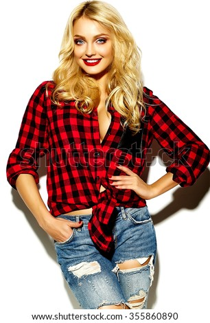 portrait of beautiful happy cute smiling blonde woman bad girl in casual red hipster winter checkered flannel shirt and blue jeans clothes with red lips  - stock photo