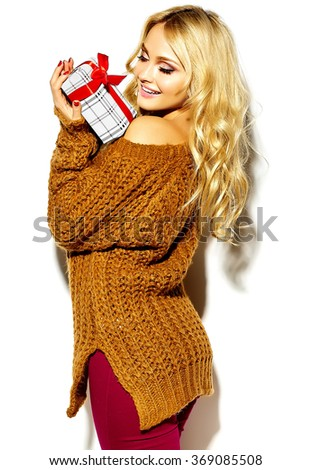 portrait of beautiful happy cute smiling blonde woman girl holding in her hands Christmas gift box in casual brown hipster winter sweater clothes - stock photo