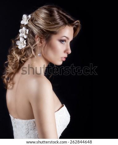 portrait of beautiful happy gentle women bride in a white wedding dress c beautiful salon wedding hair with white flowers in her hair - stock photo