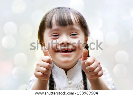 Portrait of beautiful happy girl giving thumbs up. - stock photo