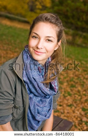 Portrait of Beautiful happy girl outdoors in the park at autumn. - stock photo