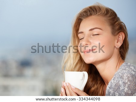 Portrait of beautiful happy girl with closed eyes, enjoying tasty strong morning coffee aroma, having breakfast in outdoor cafe - stock photo
