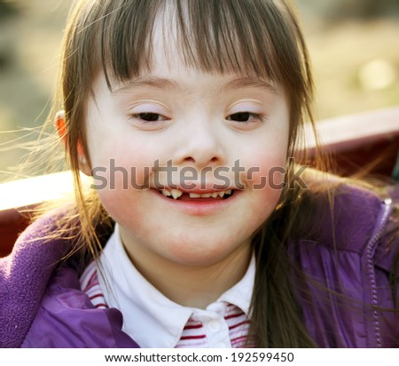 Portrait of beautiful happy girl with Downs Syndrome. - stock photo