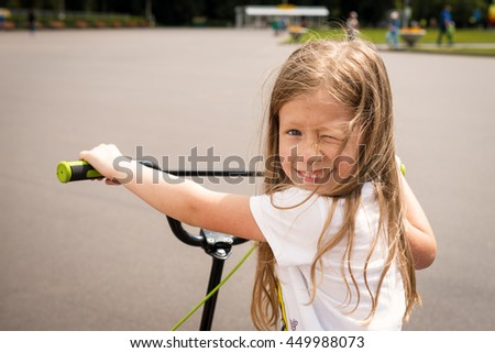 Portrait of beautiful happy little girl on a scooter in a park