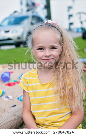 Portrait of beautiful happy little girl with long hair on the playground - stock photo