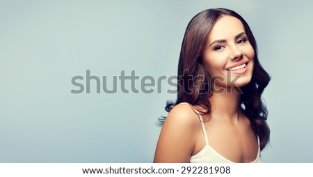 Portrait of beautiful happy smiling young brunette woman, with blank copyspace area for text or slogan - stock photo