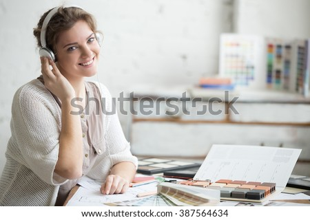 Portrait of beautiful happy smiling young designer woman sitting in headphones at home office desk, working in loft interior. Attractive cheerful model posing with friendly expression, copyspace - stock photo