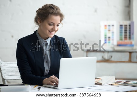 Portrait of beautiful happy smiling young designer woman working on laptop at office desk. Attractive cheerful model using computer. Typing indoors