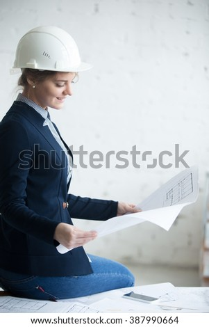 Portrait of beautiful happy smiling young engineer woman in white hard hat sitting on office desk in architectural agency. Attractive model holding project plan, looking at blueprint, planning work - stock photo