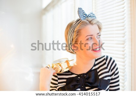 Portrait of beautiful happy smiling young pinup woman showing alarm clock standing by the bright sunny window
