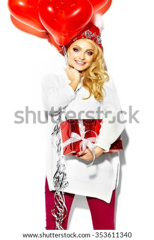 portrait of beautiful happy sweet smiling blonde woman girl holding in her hands big Christmas gift box and heart balloons in casual red hipster winter clothes, in white warm sweater  - stock photo