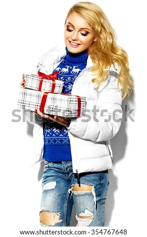 portrait of beautiful happy sweet smiling blonde woman girl holding in her hands big Christmas gift boxes in casual hipster winter warm clothes, in blue sweater  - stock photo
