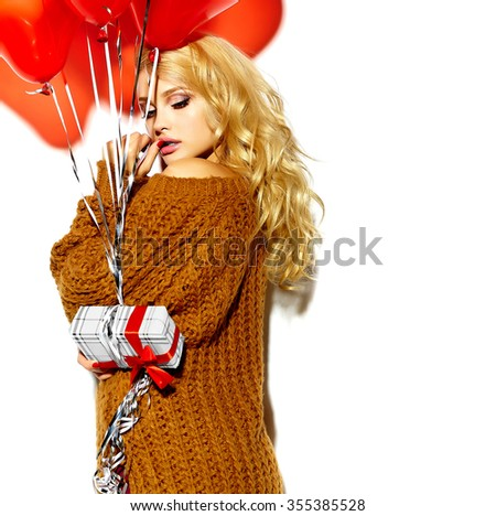 portrait of beautiful happy sweet smiling blonde woman girl holding in her hands Christmas gift box and heart balloons in casual brown hipster winter sweater clothes - stock photo