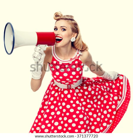 Portrait of beautiful happy woman holding megaphone, dressed in pin-up style red dress in polka dot and white gloves. Caucasian blond model posing in retro fashion and vintage concept studio shoot.