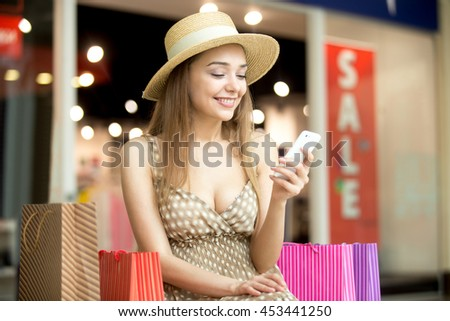 Portrait of beautiful happy woman wearing hat and dress sitting in shopping centre with colorful shopping bags, using smartphone app, looking at screen, messaging, smiling. Red sale sign on background - stock photo