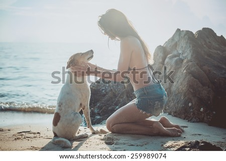 Portrait of beautiful happy young woman sitting playing with her pet dog sunset at the beach on the sea shore twilight sky as background. - stock photo