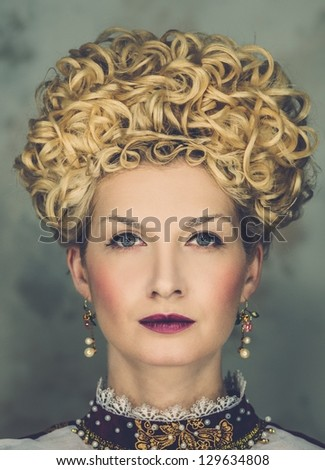 Portrait of beautiful haughty queen in royal dress - stock photo