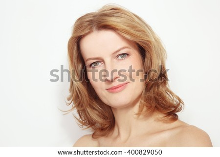 Portrait of beautiful healthy happy smiling mature woman with curly hair and clean make-up - stock photo