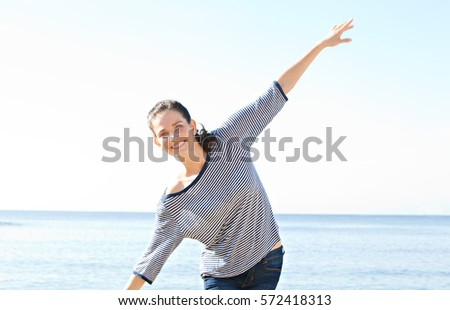 Portrait  of beautiful healthy playful woman enjoying the sun on a beach, smiling and looking rising arms up, carefree, outdoors. Wellness, health and well being lifestyle. Recreation sunny exterior.