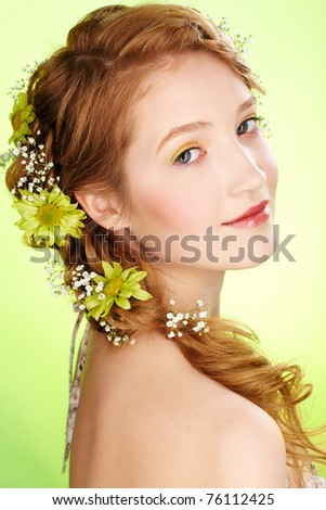 portrait of beautiful healthy redhead teen girl with flowers in her hair on green - stock photo