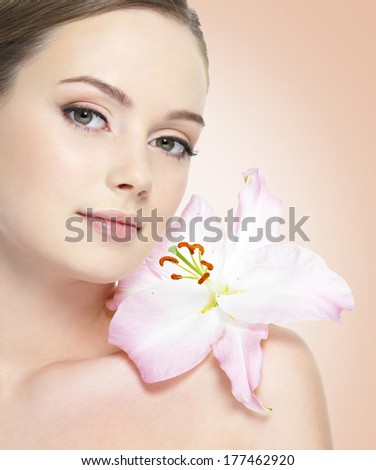Portrait of beautiful healthy woman with flower at face - stock photo