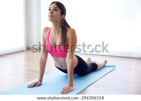 Portrait of beautiful healthy young woman doing exercise at home. - stock photo