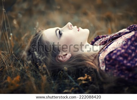 portrait of beautiful hippie girl lying on the grass - stock photo