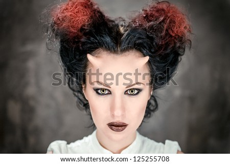 Portrait of beautiful horned woman with bright makeup, conceptual photo - stock photo