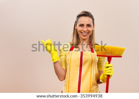Portrait of beautiful housewife holding broom and  pointing at your product.Housewife with broom pointing at your product - stock photo
