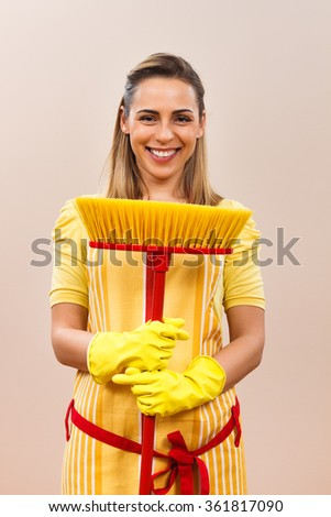 Portrait of beautiful housewife holding broom.Ready for cleaning