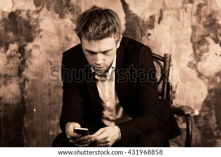 Portrait of beautiful imposing man on vintage wall background. Sits on vintage chair and looking at cell phone. Blond. Dressed in classic formal suit.  Sepia colour graded.