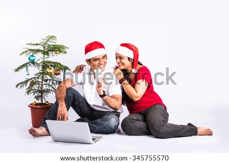 Portrait of beautiful indian couple with laptop in christmas time. Christmas tree in background. indian family and christmas time, indians with red santa hat, man showing blank card , couple on laptop - stock photo