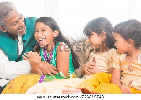 Portrait of beautiful Indian family having fun at home. Happy Asian father and children indoors lifestyle.