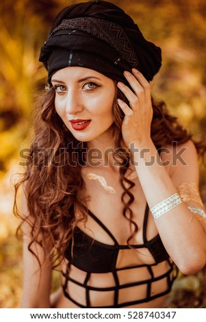Portrait of beautiful indian girl.Arabian woman portrait. Oriental girl turban. Beautiful fashion east woman portrait with oriental accessories- earrings, bracelets. Model with perfect make-up.Asia