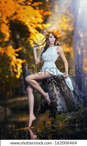 Portrait of beautiful lady in the forest. Girl with fairy look in autumnal shoot. Girl with Autumnal Make up and Hair style. Romantic women with short white dress posing in autumnal park - stock photo
