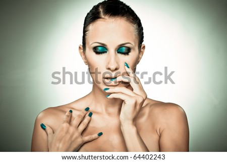 Portrait of beautiful lady showing blue nails isolated on grey in cross-process toning - stock photo