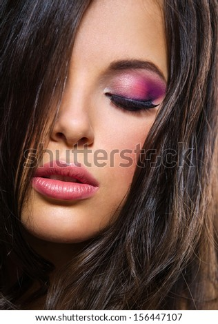 Portrait of beautiful lady with brilliant pink makeup on grey background. Concept of beauty and fashion