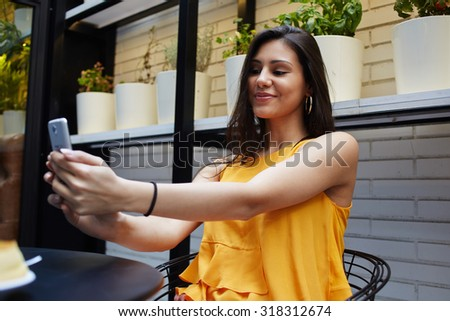 Portrait of beautiful latin woman making self portrait with mobile phone camera while sitting in modern cafe inside, charming female posing while photographing herself for social network picture