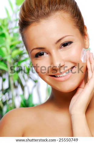 Portrait of beautiful latinos woman applying moisturiser cream - stock photo