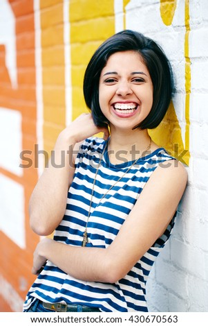 Portrait of beautiful laughing young hipster brunette latin hispanic girl woman with short hair bob, in blue jeans, striped tshirt, leaning on brick wall in city looking in camera