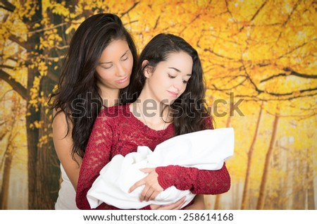 portrait of beautiful lesbian couple holding their baby over forrest background - stock photo
