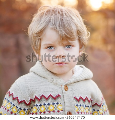 Portrait of beautiful little caucasian kid boy of 2 , outdoors. Evening light and sunset in forest. - stock photo