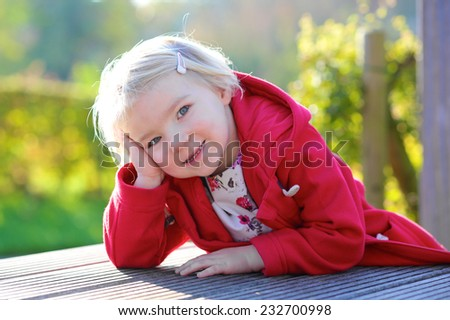 Portrait of beautiful little child, smiling blonde caucasian toddler girl in red duffle coat outdoors - stock photo