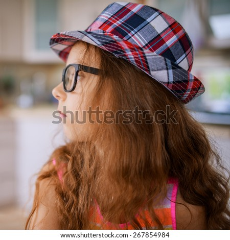 Portrait of beautiful little girl in hat and glasses on background of kitchen. - stock photo