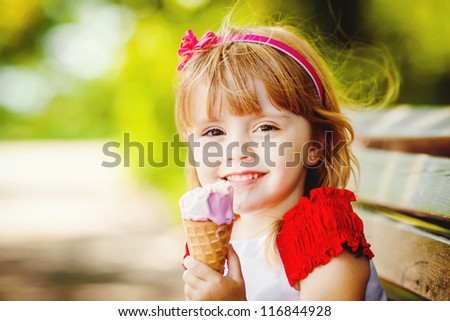 Portrait of beautiful little girl in summer green park - stock photo