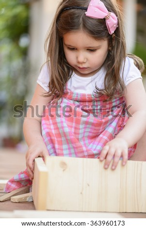 Portrait of beautiful little girl playing outside with wooden blocks, being inventive building a house for her toys