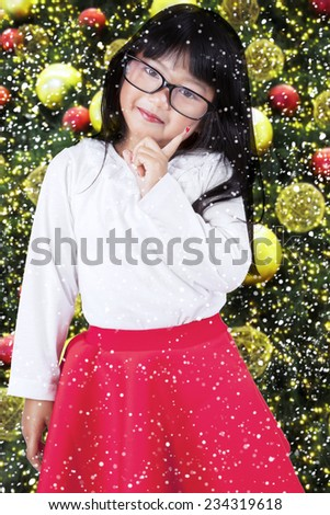 Portrait of beautiful little girl standing near christmas tree while posing and looking at camera - stock photo